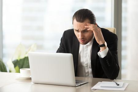 Verstoor verwarde zakenman die laptop het scherm bekijken op het werk in modern bureau. Beklemtoonde jonge CEO die bij het bureau computer in ongeloof over ontbrekende rapportstatistieken bekijkt, gemaakte slechte fout.