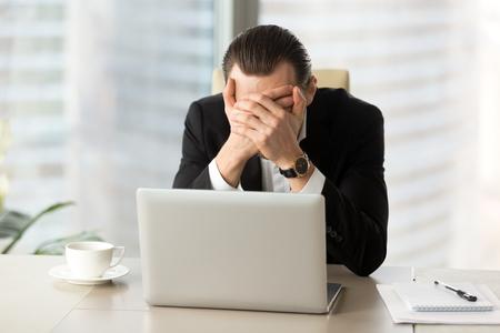 ラップトップの前で手で顔を覆う恐怖のビジネスマン。不良 CEO が悲惨な財務結果から自分自身を保護します。恐ろしいニュース、ビジネスの失敗、