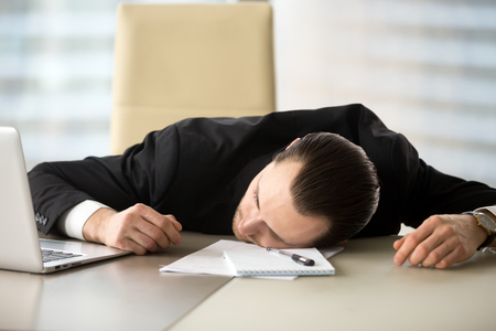 Exhausted businessman passed out at workplace desk in office. Tired entrepreneur laying on his desk in front of laptop and notes. Fatigued office employee fell asleep during work hours. Too much work Banco de Imagens