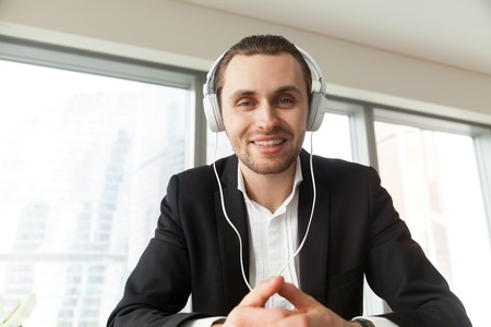 Happy businessman in headphones smiling while looking at camera. Young project manager participating in online meeting or conference with business partners, remote job interview, learning languages.