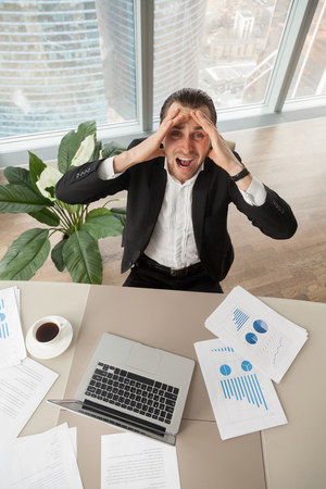 Distraught businessman at work looking up screaming in anger, with report documents, laptop, coffee on desk. CEO deranged because of financial failure. Heavy workload, profit loss, stock market crash.