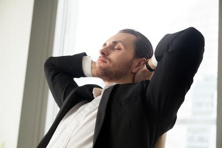 젊은 사업가 직장에서 그의 손으로 머리 뒤에 편안합니다. 성공적인 프로젝트 매니저는 오랜 근무 시간 후에 휴식을 취하고, 눈의 피로를 풀고 기업의