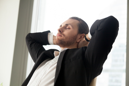 Young businessman relaxing at work with his hands behind head. Successful project manager taking break after long working hours, resting eyes from eye strain, thinking about corporate future plans.