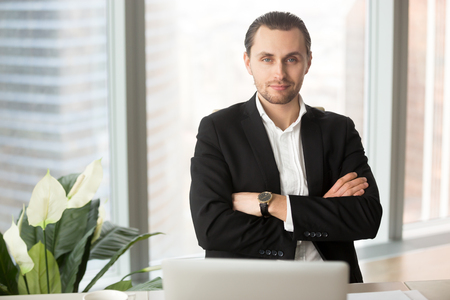 Portrait of young smiling successful businessman or entrepreneur.  Handsome young project manager, ambitious CEO posing for camera with arms crossed on chest, corporate representative at workplace. Imagens