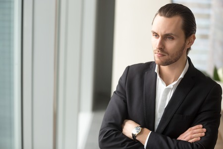 Serious young businessman standing at workplace with arms crossed on chest, in deep though about corporate future. Contemplating new investment, brainstorming about project, thinking about career.