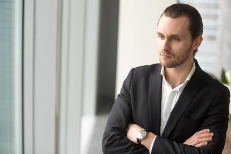 Sérieux jeune homme d'affaires debout sur le lieu de travail, les bras croisés sur la poitrine, au c?ur de l'avenir de l'entreprise Envisager de nouveaux investissements, réfléchir à un projet, réfléchir à une carrière. Banque d'images - 85683302