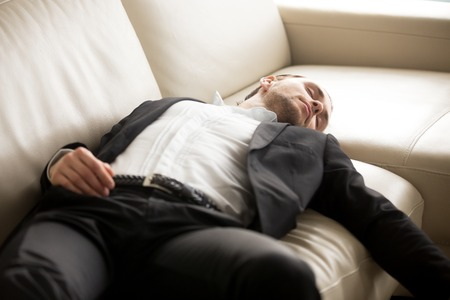 Close up of exhausted businessman laying on the couch. Young hard working entrepreneur fell asleep on sofa at workplace. Staying at work overtime, overworked, too much workload, lack of sleep concept.