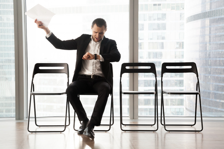 Distraught impatient businessman looking at wristwatch and yelling in anger because of tedious wait. Hand with resume document thrown in the air. Unhappy job candidate or businessman waiting too long. Reklamní fotografie