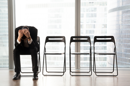 椅子に座って、待合室で、悪いニュースを受け取ったイライラ動揺ビジネスマン。ビジネスプロジェクトが失敗したために上司に解雇された CEO。人 写真素材