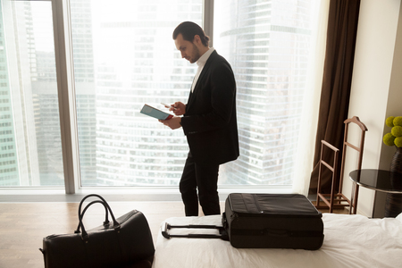 Serious businessman holds guide brochure and calls taxi or room service from hotel apartment. Traveler reads information, looks up address, orders dinner delivery. Trip or vacation concept, side view. Фото со стока - 85502143