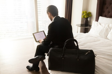 Traveling businessman sits on bed working on laptop remotely from hotel room. Business traveler finalizing important work project concept. Freelance office worker, entrepreneur. View over shoulder.