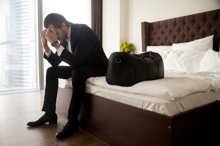 Frustrated young man in formal suit sitting on bed besides luggage bag. Businessman thinking about problems in business or at home, not feeling well, lost job, relationships or work related stress. Stock Photo - 85829978