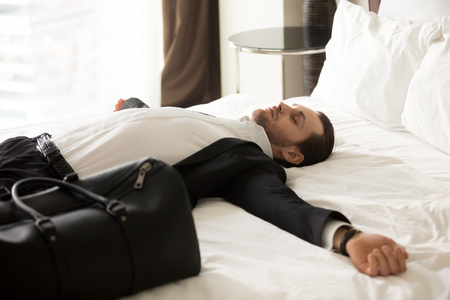 Exhausted young businessman laying with outstretched arms on bed next to small suitcase in hotel room. Entrepreneur tired after traveling, jet lag. Relieved business worker resting after long flight.