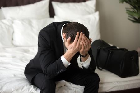Benadrukt boos man in formele pak zittend op bed met de handen op zijn hoofd, met hoofdpijn of migraine. Persoon in wanhoop. Zakelijke deal ging fout, financieel verlies, ontslagen, niet goed gevoel concept. Stockfoto