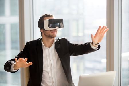 Businessman in futuristic vr headset touches air, immersed in virtual reality. Young office worker using innovative method of gaming experience or managing business project through augmented reality.