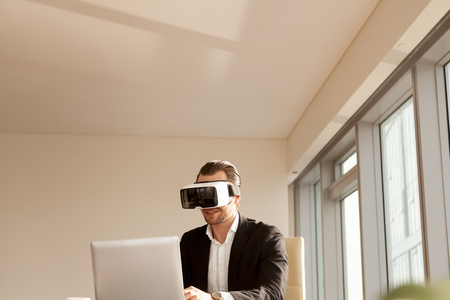 Smiling businessman in vr headset testing app on laptop. Office worker or CEO immersed in virtual reality, innovative method of browsing web or managing business project through augmented reality. Фото со стока