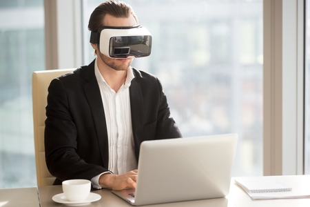 Businessman in VR headset performs application test on computer in modern office. Office worker or CEO wears futuristic goggles testing new virtual reality game or app. Innovative technology at work.