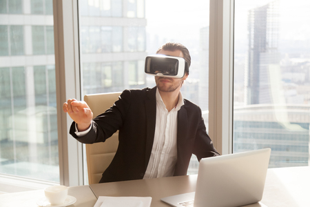 Businessman in VR headset glasses pointing finger in air. Office worker or CEO immersed in virtual reality, innovative method of browsing web or managing business project through augmented reality ar. Фото со стока