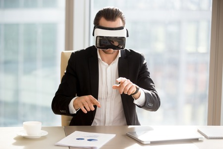 Businessman in vr headset goggles working in augmented reality at workplace. Young office worker or entrepreneur immersed in virtual reality, using innovative technology, managing business projects. Фото со стока