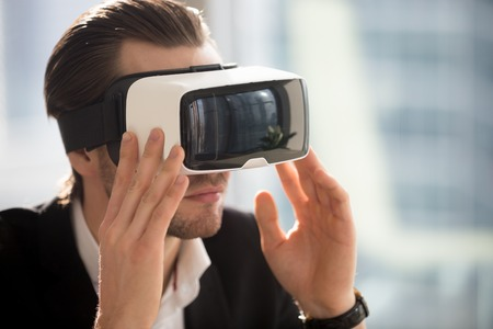 Young businessman wearing vr glasses. Young office worker, entrepreneur or CEO immersed in virtual reality, innovative method of browsing web, managing business project through augmented reality.