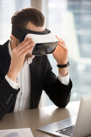 Businessman wears vr headset, immersed in virtual reality looking at laptop screen. Young office worker, entrepreneur using innovative technology, tests new applications, manages business projects. Фото со стока