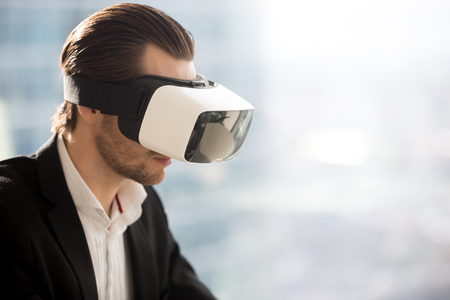 Young businessman wearing vr glasses. Office worker or CEO immersed in virtual reality, innovative method of browsing web, managing business project through augmented reality. Copy space to right.