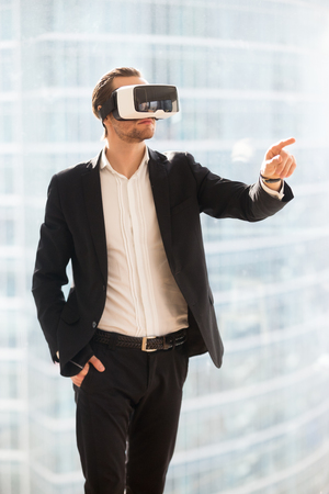 Businessman in VR glasses pointing finger in the air. Office worker or CEO immersed in virtual reality, innovative method of browsing web or managing business project through augmented reality. Фото со стока
