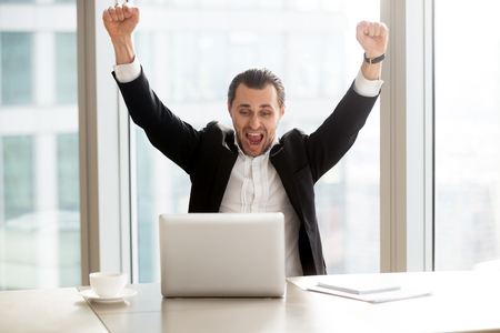 Happy handsome businessman in front of laptop at desk in modern office setting celebrating great news, screaming in joy because of victorious achievement. Successful deal, business success concept. Reklamní fotografie
