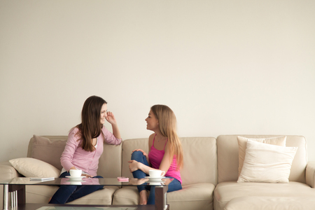 Two young girlfriends sitting on sofa at home and having personal conversation. Girls relax and chat about different topics. Best friends have cup of coffee, female friendship. Copy space for text.