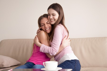 Two happy smiling young girlfriends give each other big hug. Sisters hug each other after long time being apart. Best friends reconciling after argument, forgiveness, happy to see each other concept.