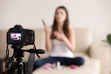 ソファに座っている若い女性 videoblogger は、ビデオの個人的なブログのための商業の美容製品レビューを記録します。ビデオブロガーは、人気のある
