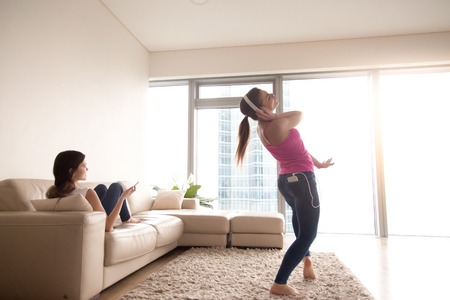 Young happy attractive girl in stylish white headphones listening and dancing to favorite music on smartphone in sunny living room at home. Joyful girlfriend relaxing on sofa with cellphone in hand. Stock Photo