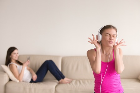Young girl in stylish white headphones listening to favorite music and singing, making funny face. Her girlfriend relaxing on sofa with smartphone in hand, laughing at her friend for being silly. Stock Photo