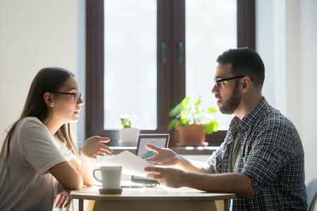 두 불만족 된 기업인 새로운 프로젝트를 논의하는 분쟁. 종이를 들고 마지막 임무에서 실수에 대해 여자에게 묻는 남자, 계약 조건에 동의하지 않는다,