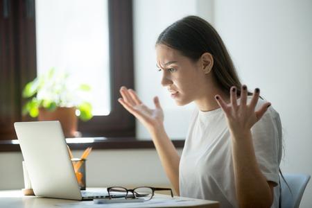 De millenial generatie jonge volwassen vrouw die in laptop computer kijkt, gooit wapens omhoog. Ze heeft net een fout gevonden bij de laatste toewijzing, een fout in het contract, onenigheid in e-mail of een bericht van ontevreden koper. Stockfoto