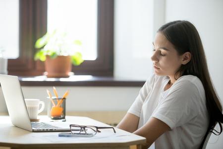 Empleada que se relaja en su lugar de trabajo, estirando los hombros y la espalda, manteniendo los ojos cerrados. Mujer tomando un descanso minuto del trabajo, sentado cerca de la ventana de la oficina. Foto de archivo - 87118436