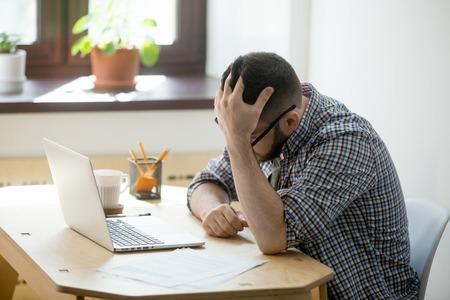 Deprimierter Mann, der in seiner Laptop-Computer erhält schlechte Nachrichten schaut. Seine Hand hält seinen Kopf in einer traurigen Geste. Konkurs- oder Entlassungskonzept. Seitenansicht.