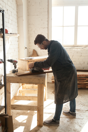 Carpenter polishes wooden boards with belt sanding machine while working in workshop. Young man choosing working profession at time of shortage skilled labor trades. Male millennial first job concept