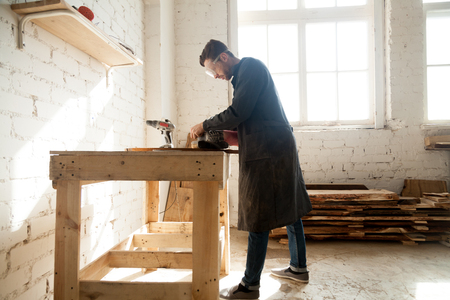 Joiner using electric tools while working in carpentry. Millennial worker getting on-the-job trailing in woodworking workshop, improve his skills in profession. Short-term job opportunities concept 版權商用圖片