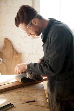 Skilled professional carpenter in workwear and protective eyewear sanding wooden plank, using electric belt sander, custom woodworking job, young craftsman grinding wood on table at workshop, vertical