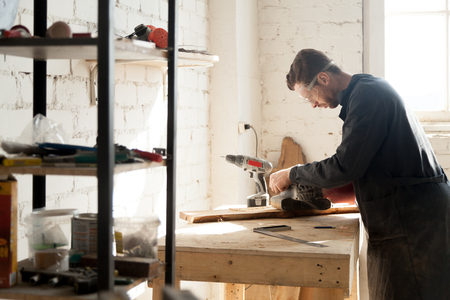 Side view of young serious joiner sanding planks, man in work clothes and protective glasses processing wood at his workshop with equipment. Carpentry services for construction, renovation and repair