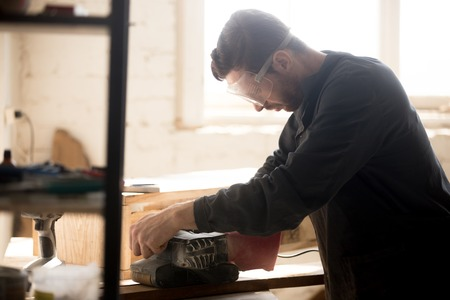 Side view of young joiner wearing protective glasses for safety sanding planks, skilled workman carpenter woodworking in small workshop with equipment tools, building and repairing wooden structures.
