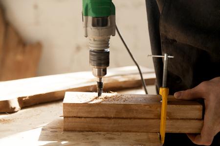乾いた木の 2 つの部分のクローズ アップ写真は、ワークベンチでクランプを固定し、電気ドリルで掘削します。建具大工のワーク ショップでの作業