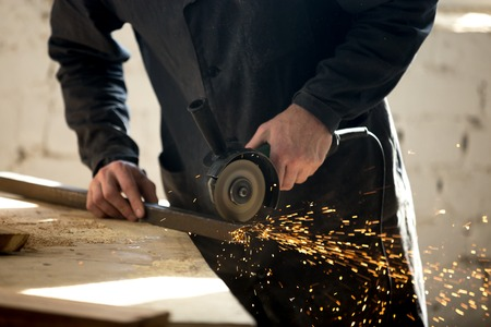 Close up photo of angle grinder in workers hand cutting metal profile on workbench with sparks. Craftsman working with electric tool in workshop. Professional equipment and instrument for metal works
