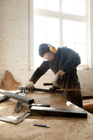Skilled young man in protective clothes cleans metal profiles on workbench with angle grinder. Craftsman making his new project in workshop. Small business owner working on his home based manufacture