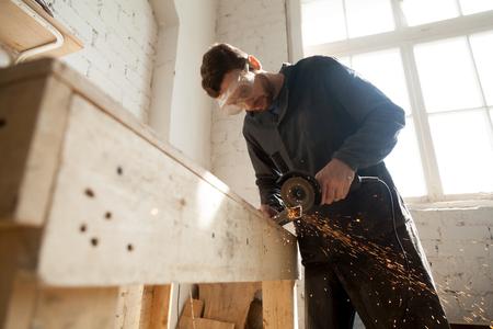 家具を作る保護メガネ死ぬアングル グラインダーを用いた切断棒鋼、研削砥石ディスク盤の金属から火花を投げる小さな工房インテリアでの作業の