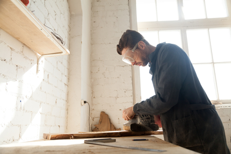 Carpenter in protective glasses polishes wooden board with handle belt sanding machine on workbench in workshop. Small business owner working in his manufacturing. Joiner made custom wooden furniture Фото со стока