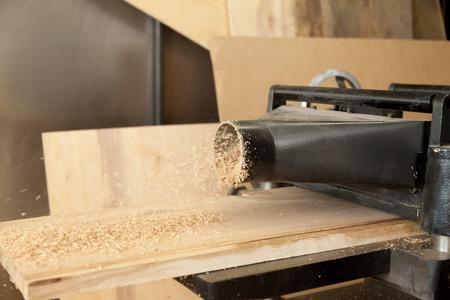 Sluit omhoog beeld van de snijplank van de dikteschaafmachine van hard hout in workshop. Het produceren van timmerhout in timmerfabricage met krachtige werktuigmachine. Professionele houtbewerkingsapparatuur voor houtzagerijen