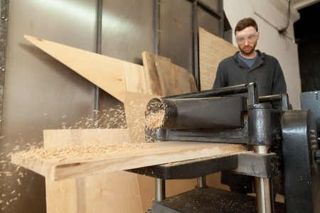Young skilled carpenter in protective eyewear operating stationary planer machine in small shop, working with wooden plank, making shredded wood as a result of trimming boards to consistent thickness Reklamní fotografie
