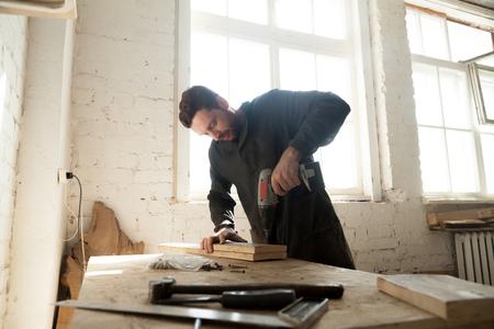 建具は、ワークベンチに木の板を電動ドリルで掘削します。若い大工はカスタム キャビネット、ワーク ショップで働く古物家具の修理します。パー 写真素材